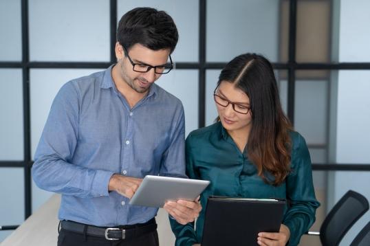 Caucasian supervisor helping new Asian employee